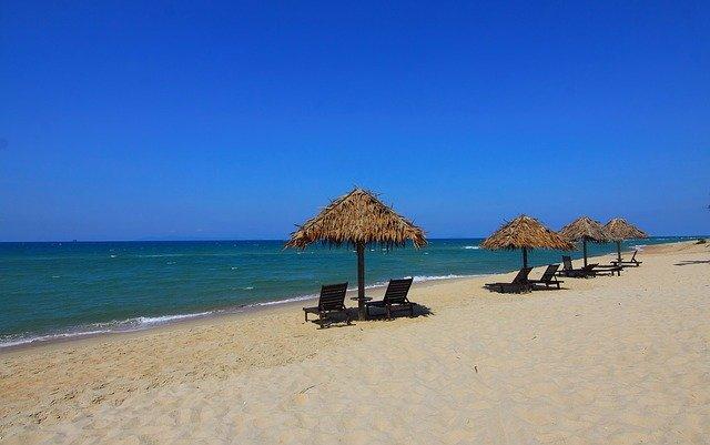 pláž se slunečníky a lehátky