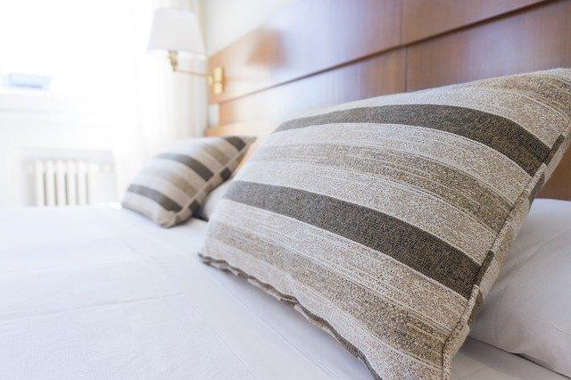 šedě pruhované polštáře na posteli