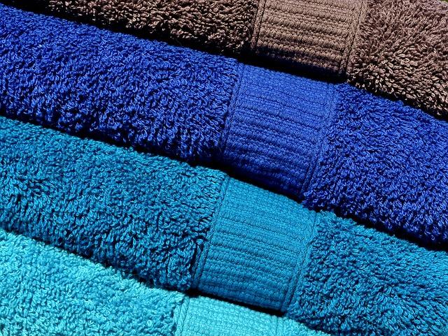 Ručníky ve škále modré barvy poskládané do komínku