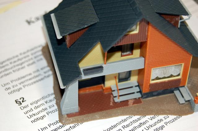 Smlouva, na které stojí vyrobený malý domeček z plastu s černou střechou a oranžovými cihlami