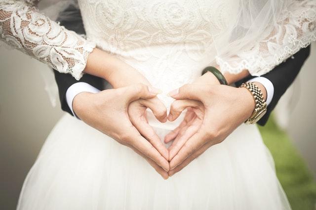 Ruce ženicha a nevěsty spojené v srdce