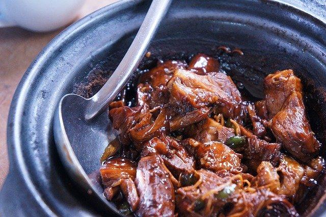 Dušené kostky hovězího masa na starém modrém keramickém talíři