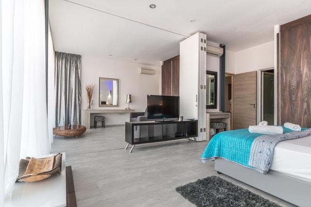obývací pokoj a ložnice, šedá podlaha, skříň, televize, na posteli modrý přehoz.jpg