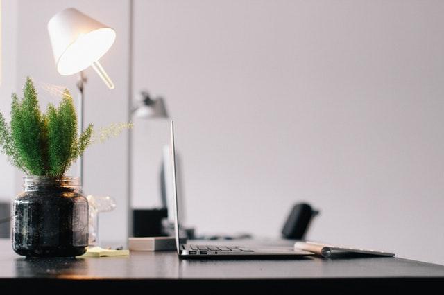 stůl se svítící lampou a notebookem, zelená květina v tmavém skleněném květináči.jpg